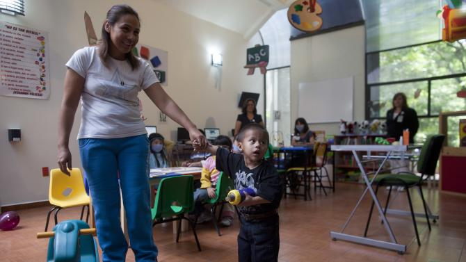 Jesus Rodriguez, 2, holds onto the hand of his mother Maria Fernandez, in a play area of La Raza Medical Center, in Mexico City, Tuesday, June 26, 2012. Mexican doctors successfully removed a 33 pound (15 kg) benign tumor protruding from the boy's right side, connected to the body from the armpit to the hip, and weighed more than Jesus. (AP Photo/Esteban Felix)