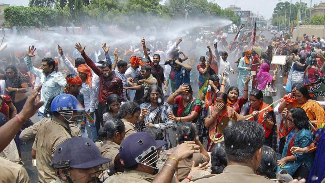 Supporters of BJP shout slogans as police use a water cannon to stop them from moving towards the office of Yadav, chief minister of Uttar Pradesh, during a protest against recent rape and hanging of two girls, in Lucknow