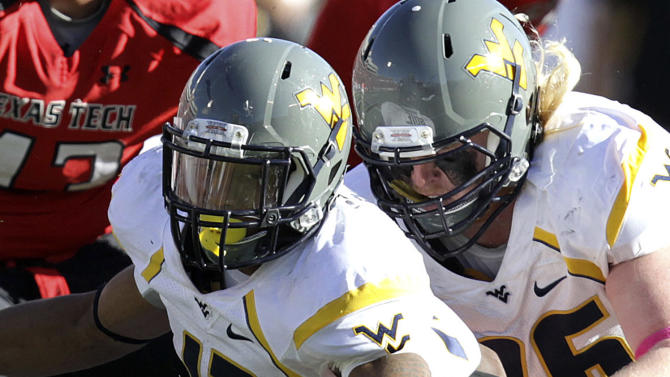 West Virginia's Andrew Buie, center, fumbles the ball after a hit by Texas Tech's Kerry Hyder, bottom, during their NCAA college football game in Lubbock, Texas, Saturday, Oct. 13, 2012. (AP Photo/Lubbock Avalanche-Journal, Scott MacWatters) LOCAL TV OUT