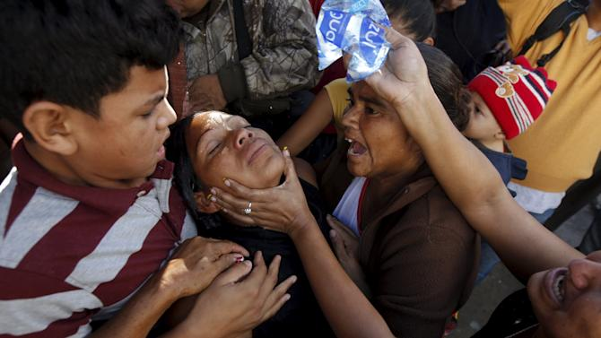 Residents help a relative of a slain victim at a crime scene where seven men were killed, in Tegucigalpa