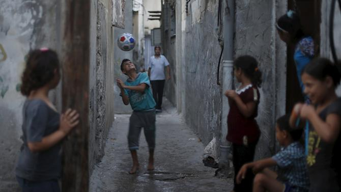 A Palestinian boy plays football outside his family house at Shatti (beach) refugee camp in Gaza City