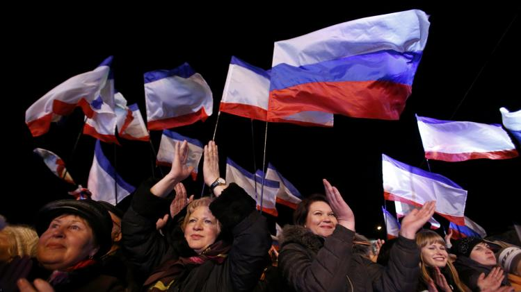 People wave Russian and Crimean flags as they wait for the announcement of preliminary results of today's referendum on Lenin Square in the Crimean capital of Simferopol