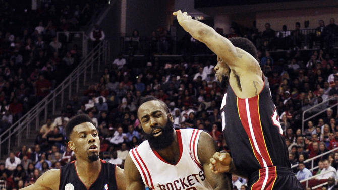 Houston Rockets' James Harden (13) heads to the basket between Miami Heat's Norris Cole (30) and Udonis Haslem (40) in the second half of an NBA basketball game, Monday, Nov. 12, 2012, in Houston. The Heat won 113-110. (AP Photo/Pat Sullivan)