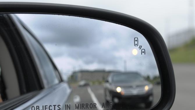 FILE - This May 22, 2012 file photo shows a side mirror warning signal in a Ford Taurus at an automobile testing area in Oxon Hill, Md. Federal officials are planning to announce Monday whether automakers should be required to equip new cars and light trucks with technology that enables vehicles to communicate with each other to prevent collisions. Such vehicle-to-vehicle communication could eventually transform traffic safety. (AP Photo/Susan Walsh, File)
