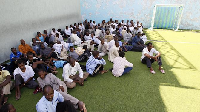 """Men suspected of being mercenaries for Moammar Gadhafi, are held in a district sports center next to the medina, set up as provisory jail in Tripoli, Libya, Tuesday, Aug. 30, 2011.  Libyan rebels are demanding that Algeria return Moammar Gadhafi's wife and three of his children for trial after they fled, raising tensions between the neighboring countries. Algeria's decision to host members of the Gadhafi clan is an """"aggressive act against the Libyan people's wish,"""" said Mahmoud Shammam, information minister in the rebels' interim government.(AP Photo/Francois Mori)"""