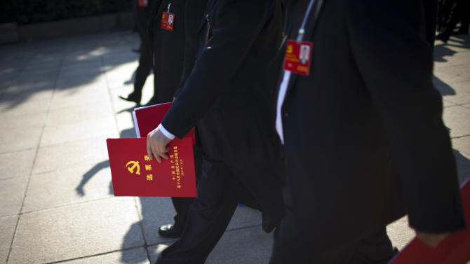 Chinese Communist Party delegates hold red voting ticket holders while they leave the Great Hall of the People after the closing ceremony for the 18th Communist Party Congress in Beijing, China, Wednesday, Nov. 14, 2012. President Hu Jintao has stepped aside as Communist Party leader to clear the way for Vice President Xi Jinping to take the helm in China. (AP Photo/Alexander F. Yuan)