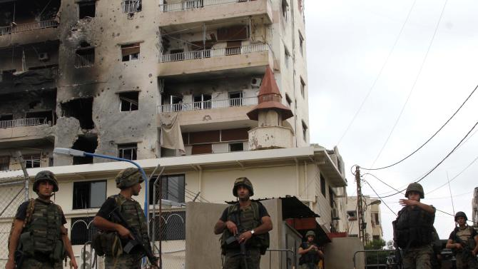 Lebanese army soldiers stand guard near the Bilal bin Rabbah mosque where Sunni cleric Sheik Ahmad al-Assir preaches, in the southern port city of Sidon, Lebanon, Tuesday, June 25, 2013. Lebanese security officials say a roadside bomb has exploded on the highway linking Beirut with the Syrian capital without causing casualties. (AP Photo/Mohammed Zaatari)