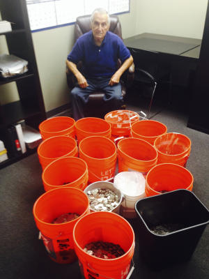 This image provided by Andres Carrasco shows him in his office in Los Angeles, July 31, 2014 with buckets of change he won as a partial settlement in a 2012 lawsuit against Adriana's Insurance Services, a Rancho Cucamonga, Calif.-based company. The insurance company settled with Carrasco, by dropping off buckets full of thousands dollars in quarters, nickels, dimes and pennies. (AP Photo