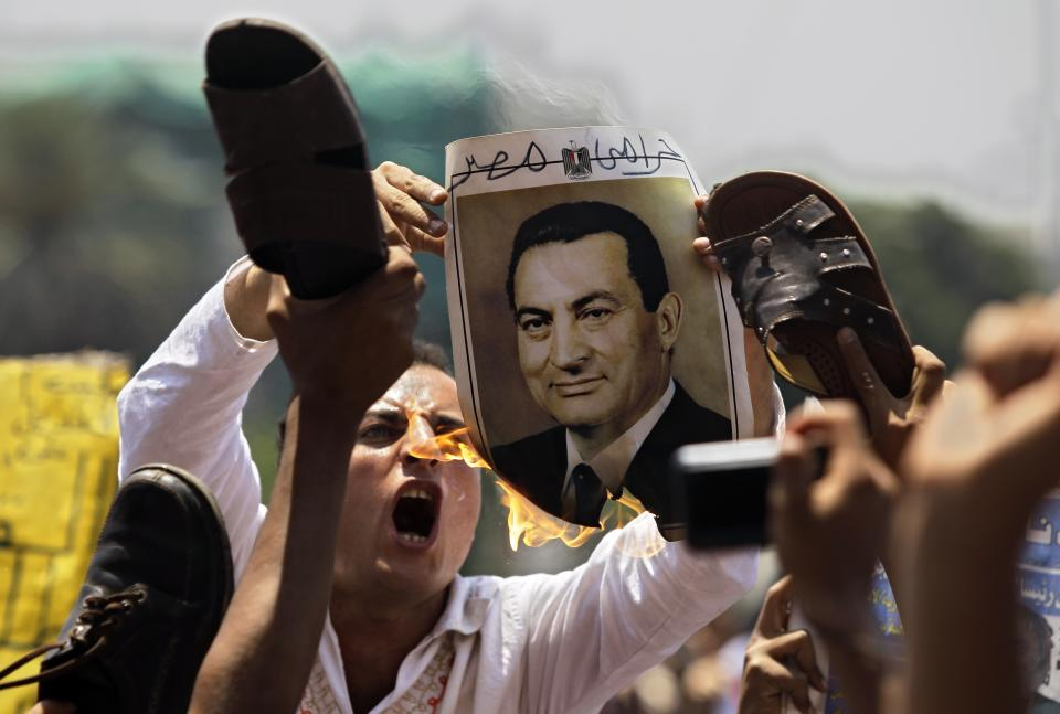 A man burns a picture of ousted Egyptian president Hosni Mubarak as others symbolically brandish a shoe at the image, their during a rally after Friday prayers in Tahrir Square, Cairo,  Friday, July 1, 2011.  (AP Photo/Sergey Ponomarev)