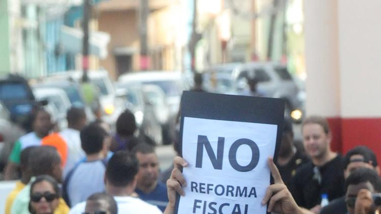 "Dominicans attend a demonstration against the fiscal reform in Santo Domingo, Dominican Republic, Sunday, Nov. 11, 2012. Hundreds of Dominicans protested against the government of Danilo Medina who presented to Congress the disputed tax legislation as a way to help close the $4.6 billion deficit in the government's budget. The measure will increase the general sales tax to 18 percent from 16 percent, will raise the price of gasoline and impose taxes on basic food products. The sign reads in Spanish: ""No to fiscal reform"". (AP Photo/Manuel Diaz)"