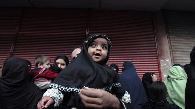 A Pakistani Shiite Muslim baby girl is held by her mother during a Muharram procession in Peshawar, Pakistan on Saturday, Nov. 24, 2012. Muharram is a month of mourning in remembrance of the martyrdom of Imam Hussein, the grandson of Prophet Mohammed. (AP Photo/Mohammad Sajjad)