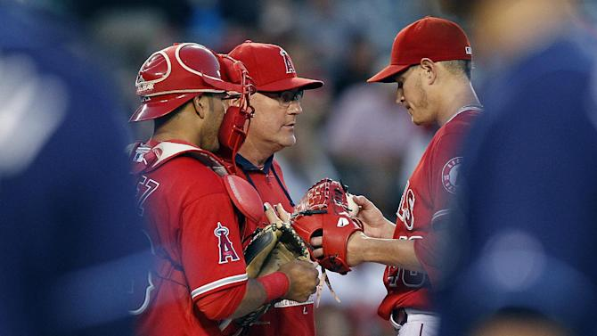 Los Angeles Angels pitching coach Mike Butcher, center, talks to starting pitcher Garrett Richards, right, with catcher Carlos Perez in on the conversation during the third inning of a baseball game against the Tampa Bay Rays in Anaheim, Calif., Monday, June 1, 2015. (AP Photo/Alex Gallardo)