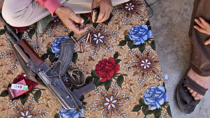 A Syrian rebel fighter prepares his AK-47 before going on patrol in Marea, on the outskirts of Aleppo, Syria, Tuesday, Sept. 4, 2012. (AP Photo/Muhammed Muheisen)