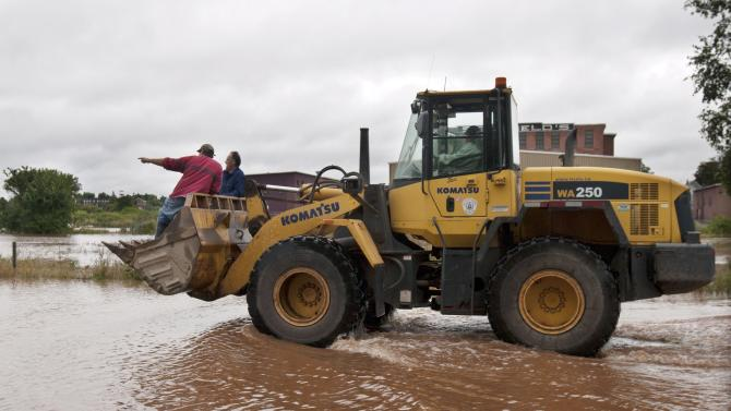 Workers head to the Colchester Legion Stadium after dikes on the Salmon River gave way, Monday, Sept. 10, 2012. The area is under a rainfall warning as Tropical Storm Leslie churns toward Atlantic Canada. Leslie is expected to make landfall in Newfoundland bringing heavy rain and high winds. (AP Photo/The Canadian Press, Andrew Vaughan)
