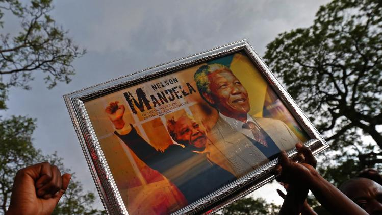 Mourners hold a picture of former South African President Nelson Mandela while dancing and singing in Pretoria