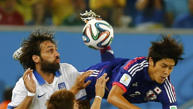 Japan's Uchida is fouled by Greece's Samaras during their 2014 World Cup Group C soccer match at the Dunas arena in Nata