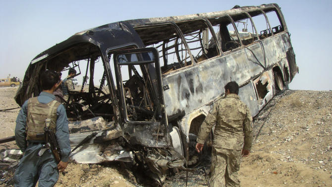 Afghan police and army soldiers inspect a burned bus after it collided with the wreckage of a truck that was attacked by Taliban insurgents in Maiwand district, on the highway between Kandahar and Helmand, Afghanistan, Friday, April 26, 2013. Scores of people aboard the bus were killed in the fiery crash, officials said. (AP Photo/Abdul Khaliq Kandahari)