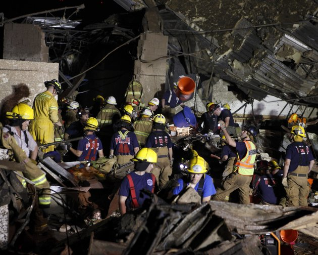 Oklahoma National Guard soldiers and rescue workers dig through the rubble of Plaza Tower Elementary school after a devastating tornado ripped through Moore