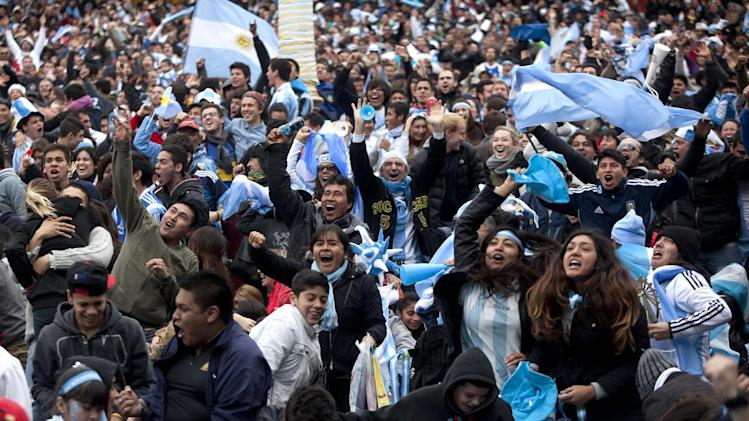 Argentina soccer fans celebrate Messi's winning goal against Iran at the Brazil World Cup as they watch the game on an outdoor screen set up in Buenos Aires, Argentina, Saturday, June 21, 2014