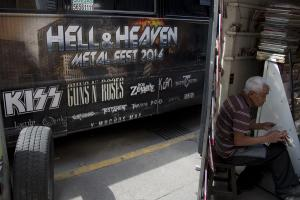 """A man reads a newspaper next to publicity of """"Hell…"""