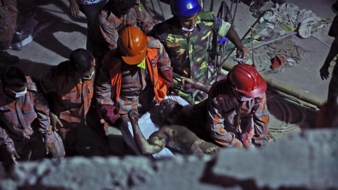 Bangladeshi soldiers and firefighters carry a burned and injured colleague after a fire in a tunnel that rescue workers were using to search for survivors in a building that collapsed Wednesday in Savar, near Dhaka, Bangladesh, Sunday, April 28, 2013. A fire broke out late Sunday in the wreckage of the garment factory that collapsed last week in Bangladesh killing hundreds, with smoke pouring from the piles of shattered concrete and some of the rescue efforts forced to stop.(AP Photo/Kevin Frayer)