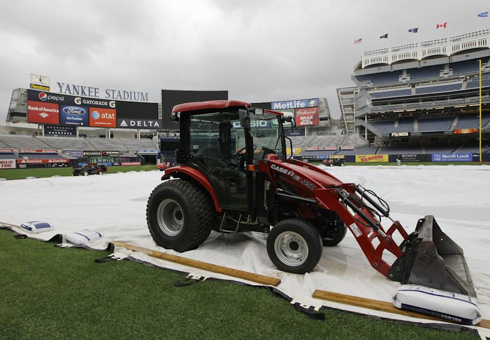A tractor sits on the tarp to prevent it from blowing away in high winds after Tuesday night's baseball game between the New York Yankees and the Toronto Blue Jays was postponed because of inclement weather, at Yankee Stadium in New York, Tuesday, Sept. 18, 2012. (AP Photo/Kathy Willens)