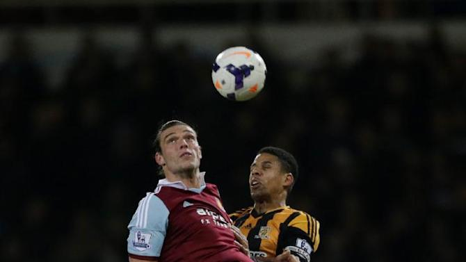 West Ham's Andy Carroll, left, competes for the ball with Hull City's Curtis Davies during the English Premier League soccer match between West Ham and Hull City at Upton Park stadium in London, Wednesday, March 26, 2014