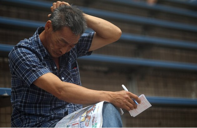 A man reads betting odds in …