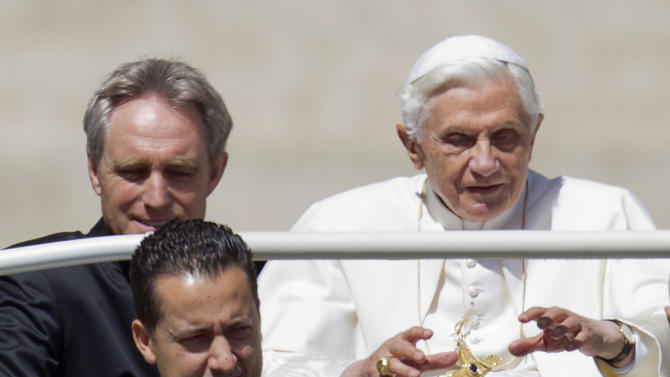 FILE -- In this photo taken Wednesday, May, 23, 2012, Pope Benedict XVI, flanked by his private secretary Georg Gaenswein, top left, and his butler Paolo Gabiele arrives at St.Peter's square at the Vatican for a general audience. Paolo Gabriele took the stand Tuesday, Oct. 2, 2012, in a Vatican courtroom to defend himself against a charge of aggravated theft. He said he is innocent of charges of stealing the pope's private correspondence but acknowledged he feels guilty of betraying the trust of the pontiff, whom he said he loved like a father. In other testimony Tuesday, the pope's private secretary, Monsignor Georg Gaenswein, testified that he began having suspicions about Gabriele after he realized three documents that appeared in the journalist's book could only have come from the office he shared with Gabriele. (AP Photo/Andrew Medichini, File)