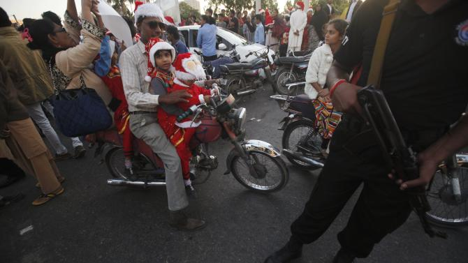 Children in Santa Claus outfits attend a rally  in Karachi in support of the victims of a Taliban attack on the Army Public School in Peshawar