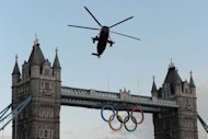 A Sea King helicopter carrying the Olympic Flame flies over London's Tower Bridge