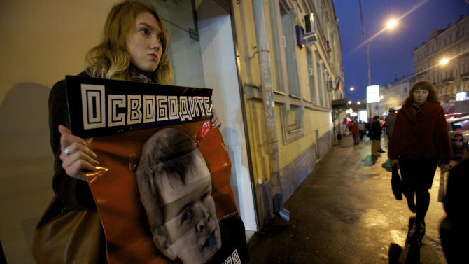 "An opposition supporter holds a poster reading ""Free Lebedev""  near the building of a court which sanctioned the arrest of  leftist activist Konstantin Lebedev in Moscow, Thursday, Oct. 18, 2012. Russia's top investigative agency filed criminal charges Thursday against  Konstantin Lebedev, an assistant of opposition leader Sergei Udaltsov, continuing a widespread crackdown on the movement against President Vladimir Putin. The Investigative Committee said in a statement that Left Front member Konstantin Lebedev has been charged with plotting mass riots and could face a jail term of up to ten years. (AP Photo/Ivan Sekretarev)"