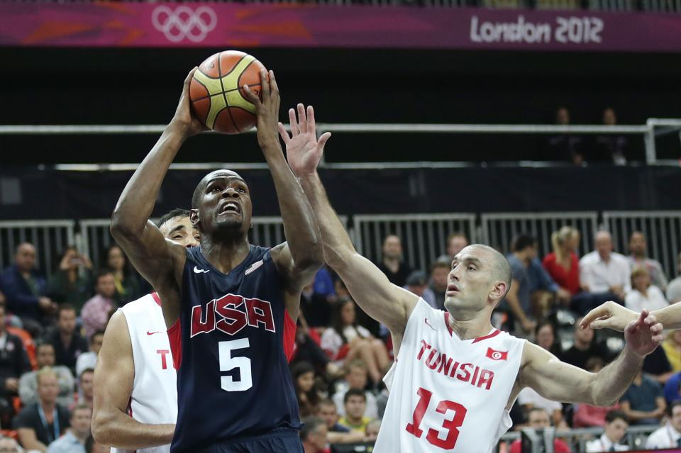USA's Kevin Durant, left, drives to the basket against Tunisia's Amine Rzig during a men's basketball game at the 2012 Summer Olympics, Tuesday, July 31, 2012, in London. (AP Photo/Charles Krupa)