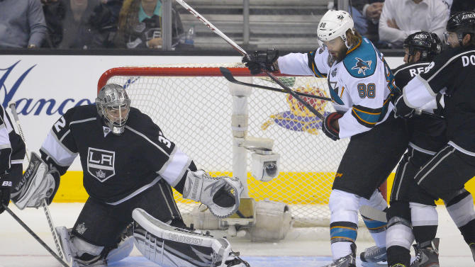 Los Angeles Kings goalie Jonathan Quick (32) makes a save as San Jose Sharks defenseman Brent Burns (88) looks on in the first period during Game 5 of the Western Conference semifinals in the NHL hockey Stanley Cup playoffs, Thursday, May 23, 2013, in Los Angeles. (AP Photo/Mark J. Terrill)