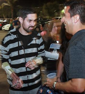 In this Friday, Mar. 29, 2013, photo, Riverside police officer Andrew Tachias, left, is greeted by Aurelio Molendez, vice president of the Riverside Police Officers Association in Riverside, Calif. Tachias, who was nearly killed in an ambush by rogue ex-cop Christopher Dorner, made his first public appearance since the shooting. Tachias was sitting in his patrol car with Officer Michael Crain on Feb. 7 when Dorner pulled alongside them at a stoplight and opened fire. (AP Photo/The Press-Enterprise, David Bauman)