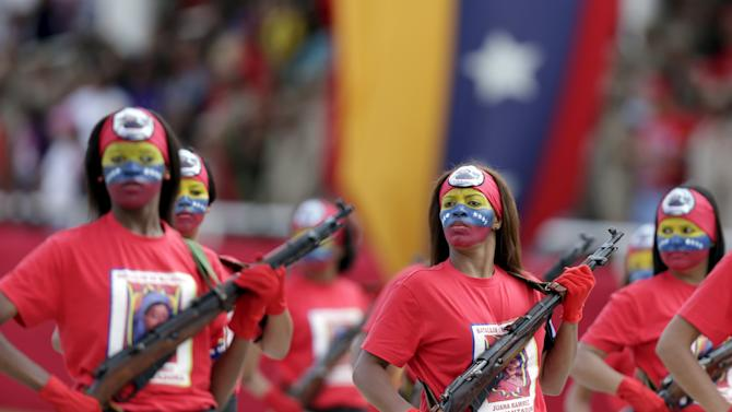 Female soldiers with their faces painted in the colours of the Venezuelan national flag, march during a military parade to celebrate the anniversary of Venezuela's independence in Caracas