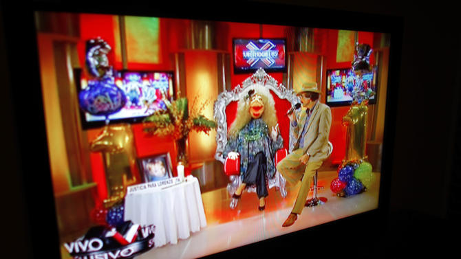"""In this Oct. 17, 2012, a TV show called """"La Comay"""" (roughly translated to """"The Godmother""""), is seen on a TV set in San Juan, Puerto Rico. This five-foot tall puppet with outlandish red lips, a shrill voice and a penchant for salacious details rules Puerto Rico's gossip circuit, with legions tuning into her show every afternoon ready for the latest bombshell. And La Comay dishes it out with ominous music playing in the background, talking about everyone from Mexican crooner Luis Miguel to Puerto Rico's own Miss Universe beauty queen Zuleyka Rivera. (AP Photo/Ricardo Arduengo)"""
