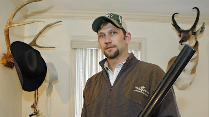 In this photo taken on Friday, April 12, 2013, Gaspar Perricone poses with one of his favorite guns at his home in Denver. Perricone co-founded The Bull Moose Sportsmen's Alliance, a group that took the unusual step earlier this month of releasing a poll that showed wide support among hunters for universal background checks. Most public polls have shown about 90 percent of voters support such a measure. (AP Photo/Ed Andrieski)