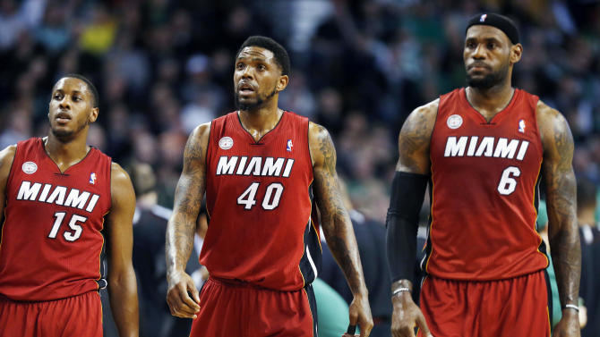 Miami Heat's Mario Chalmers (15), Udonis Haslem (40) and LeBron James (6) walk upcourt after a timeout in the first quarter of an NBA basketball game against the Boston Celtics in Boston, Monday, March 18, 2013. (AP Photo/Michael Dwyer)