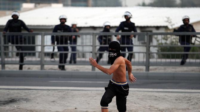 A masked Bahraini anti-government protester confronts riot police who give chase in Sanabis, Bahrain, Tuesday, Feb. 12, 2013. Clashes erupted at the end of an anti-government march, when hundreds of youths attempted to reach the heavily guarded site of the 2011 pro-democracy uprising. (AP Photo/Hasan Jamali)