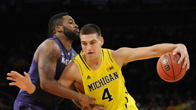 Michigan's Mitch McGary, right, drives the basket as he is guarded by Kansas State's Thomas Gipson during the first half of an NCAA college basketball game in the championship game of the NIT Season Tip-Off tournament at Madison Square Garden in New York, Friday, Nov. 23, 2012.  (AP Photo/Bill Kostroun)