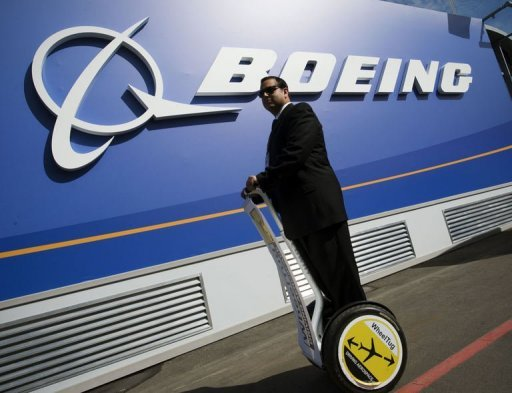 <p>A businessman rides past a Boeing chalet at the Farnborough International Airshow in Hampshire, southern England. United Airlines announced a monster order of 150 aircraft from Boeing on Thursday, a deal which the planemaker said was worth about $14.7 billion.</p>