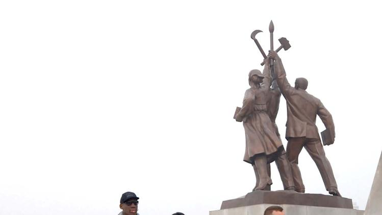 """In this image released by the Korean Central News Agency (KCNA) and distributed by the Korea News Service, former NBA star Dennis Rodman, third right, walks by the base of the Tower of the Juche Idea in Pyongyang in North Korea Friday, March 1, 2013.  Ending his unexpected round of basketball diplomacy in North Korea on Friday, ex-NBA star  Rodman called leader Kim Jong Un an """"awesome guy"""" and said his father and grandfather were """"great leaders."""" (AP Photo/KCNA via KNS) JAPAN OUT UNTIL 14 DAYS AFTER THE DAY OF TRANSMISSION"""