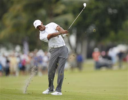 Woods hits his approach shot into the 18th green during third round play in the 2013 WGC-Cadillac Championship PGA golf tournament in Doral