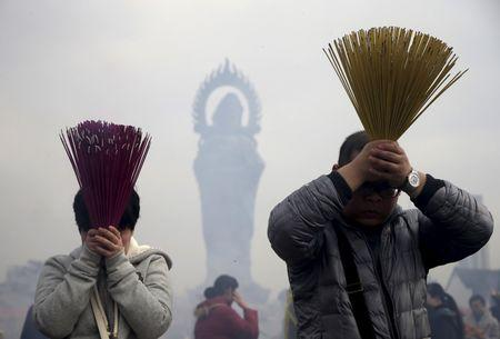 People burn incense to worship the God of Fortune at Guiyuan Temple on the fifth day of Chinese Lunar New Year in Wuhan