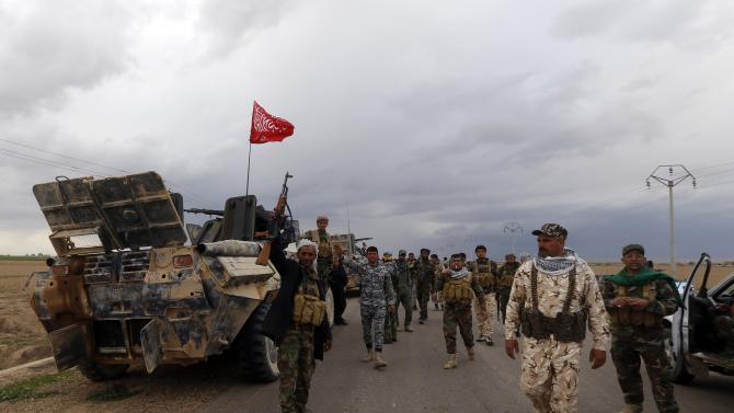 Shi'ite fighters gesture in the town of Hamrin in Salahuddin province