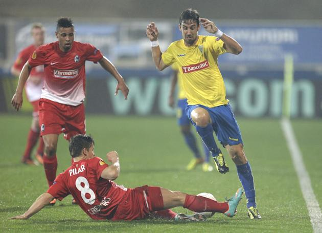 Freiburg's Vaclav Pilar, from the Czech Republic, tackles Estoril's Filipe Goncalves during their Europa League group H soccer match Thursday, Nov. 7 2013, in Estoril, Portugal