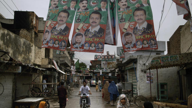 Pakistani girls, cross a street decorated with election posters showing cricket star-turned-politician, and leader of Pakistan Tehreek-e-Insaf party, Imran Khan, and other members of his party, in Rawalpindi, Pakistan, Sunday, May 12, 2013. Pakistan's former prime minister Nawaz Sharif looked set Sunday to return to power for a third term, with an overwhelming election tally that just weeks ago seemed out of reach for a man who had been ousted by a coup and was exiled abroad before clawing his way back as an opposition leader. (AP Photo/Muhammed Muheisen)