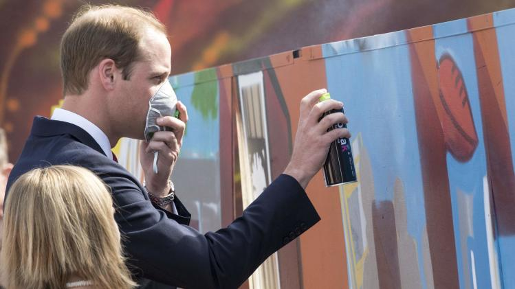 Britain's Prince William sprays paint to help create a piece of street art at The Northern Sound System, in Elizabeth near Adelaide