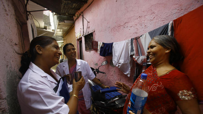 """In this Tuesday, May 21, 2013 photo, Usha Devi, right, who was suffering from cervical cancer, talks with health workers from Tata Memorial Hospital in a slum in Mumbai, India. A simple vinegar test slashed cervical cancer death rates by one-third in a remarkable study of 150,000 women in the slums of India, where the disease is the top cancer killer of women. Experts called the outcome """"amazing"""" and said this quick, cheap test could save tens of thousands of lives each year in developing countries by spotting early signs of cancer, allowing treatment before it's too late. Devi, one of the women in the study, says it saved her life.  (AP Photo/Rafiq Maqbool)"""